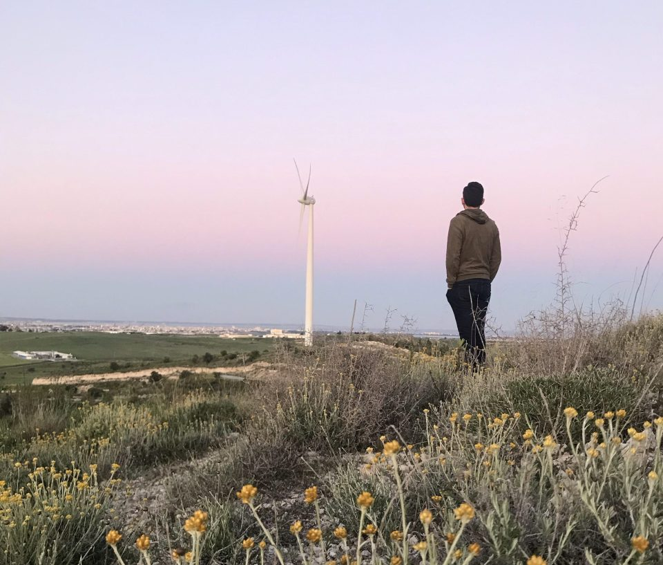 Me, yemenaris, gazing the city fear away from the hill during the sunset. At the background there is also a wind energy fan